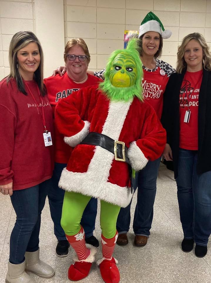 Two teachers posing with the Grinch